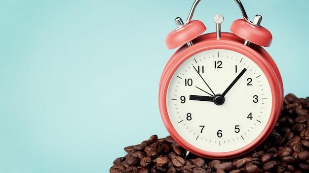 Czerwony budzik stojący w stercie ziaren kawy