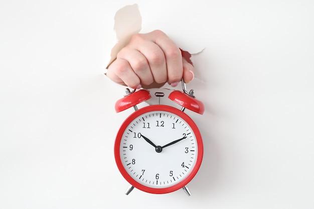 Czerwony budzik trzyma rękę przez otwór w białym papierze