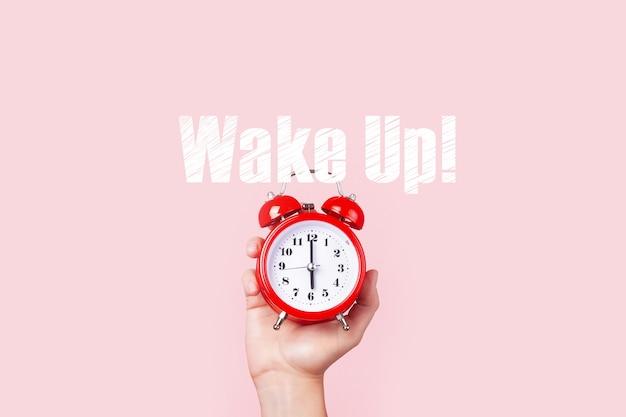 Czerwony budzik w ręku nad różową przestrzenią, obudź koncepcję
