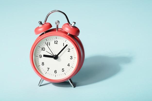 Czerwony budzik z cieniem. siedem minut po dziewiątej na zegarze