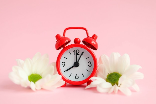 Czerwony budzik z kwiatami na różowej powierzchni