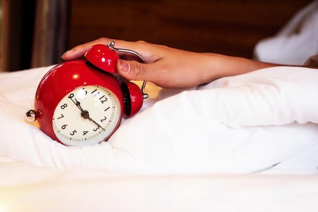 Czerwony budzik został dotknięty ręką lady