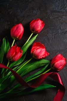 Czerwony bukiet kwiatów tulipanów z czerwoną wstążką na czarnym stole z teksturą, widok z góry na kopię miejsca