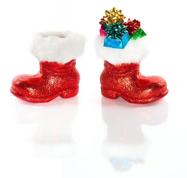 Czerwony but mikołaja z prezentami na białym tle