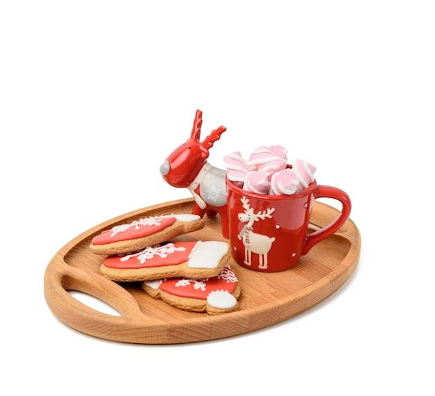 Czerwony ceramiczny kubek z kakao i piankami, białe tło