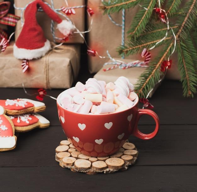 Czerwony ceramiczny kubek z kakao i piankami, za pudełkiem i świąteczną zabawką