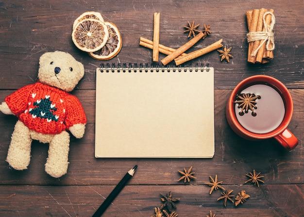 Czerwony ceramiczny kubek z kakao, notatnik z pustymi prześcieradłami i brązowy miś zabawka na drewnianym stole, widok z góry