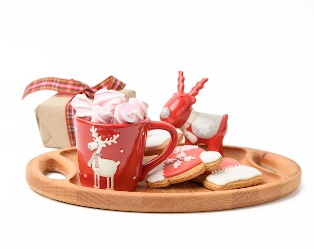 Czerwony ceramiczny kubek z napojem i piankami, przy upieczonym świątecznym pierniku, biała powierzchnia