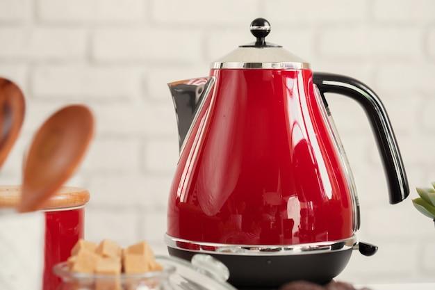 Czerwony czajnik elektryczny w stylu vintage we wnętrzu kuchni