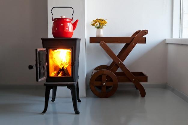 Czerwony czajnik gotujący się na kuchence retro w kuchni projekt domu wiejskiego z piecem we wnętrzu