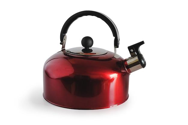 Czerwony czajnik z gwizdkiem na białym tle na białej powierzchni.