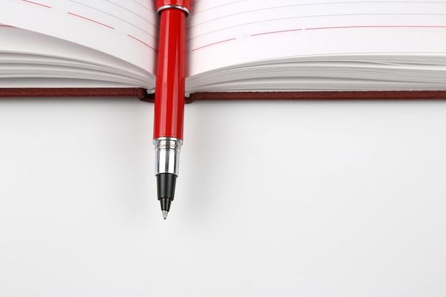 Czerwony długopis leżący na otwartym notatniku