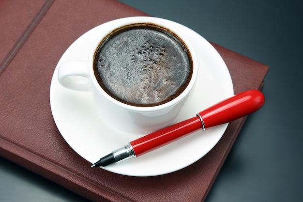 Czerwony długopis to spodek filiżanka czarnej kawy