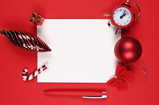Czerwony długopis z papierem na tle bożego narodzenia.
