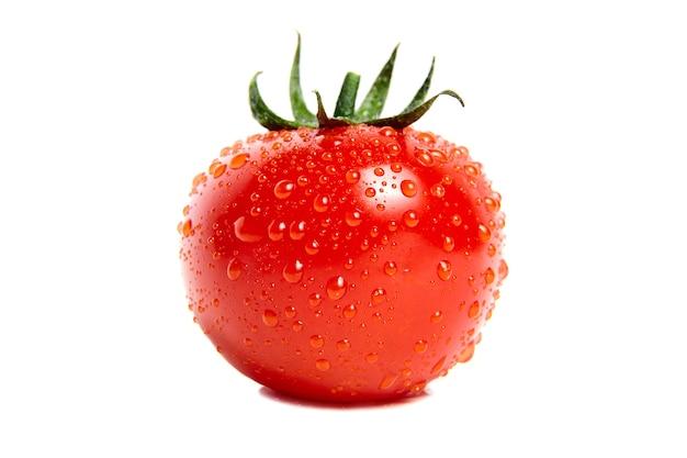 Czerwony dojrzały pomidor z kroplami wody. na białym tle