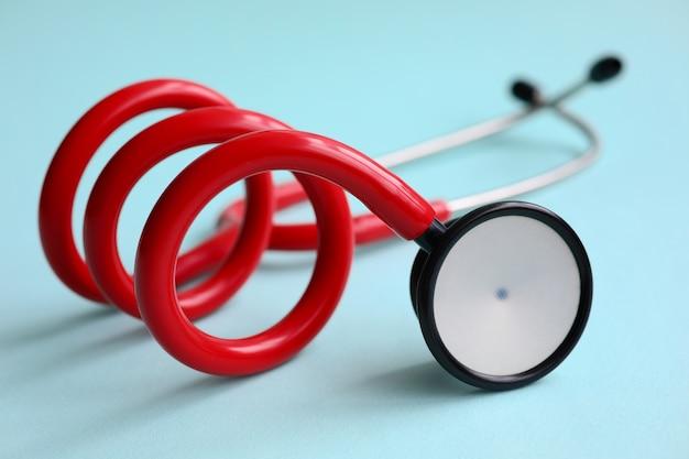 Czerwony doktorski stetoskop na błękitnym nowożytnym tle