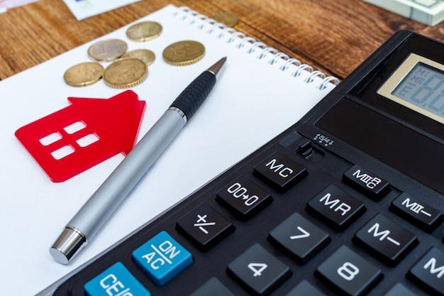 Czerwony dom, notatnik, długopis, monety i kalkulator