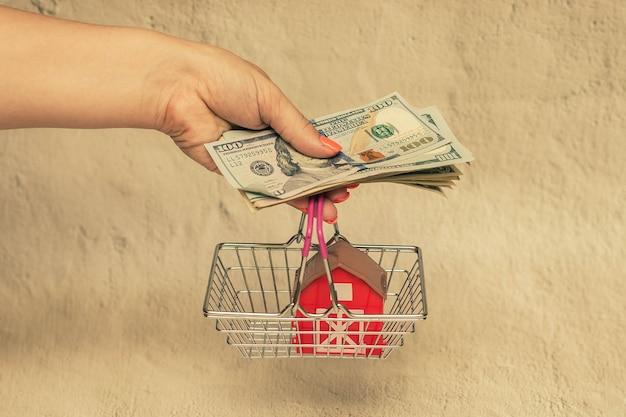 Czerwony dom w koszyku ze stosem banknotów dolarowych w dłoni koncepcja kupna domu