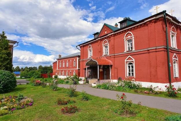 Czerwony dom w ogrodzie na tle błękitnego nieba z chmurami