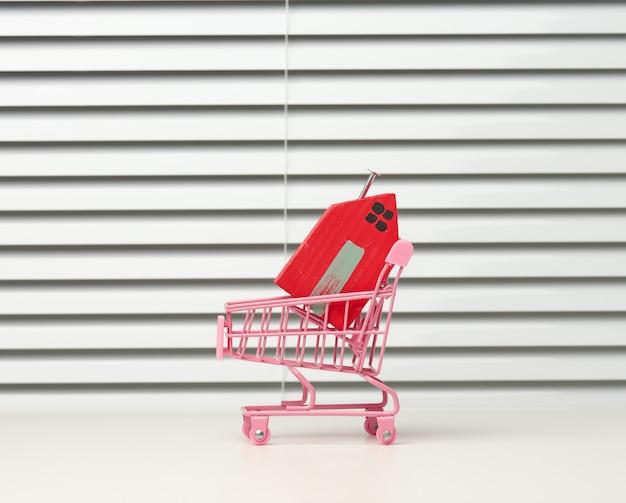 Czerwony drewniany dom w metalowym wózku miniaturowym na białym tle. koncepcja zakupu nieruchomości, hipoteka