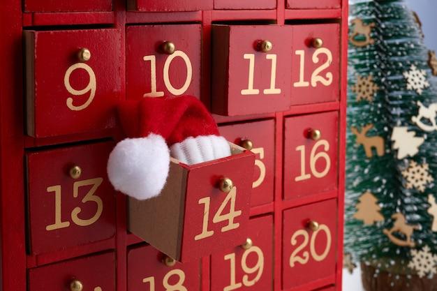 Czerwony drewniany kalendarz adwentowy z niespodzianką na boże narodzenie.