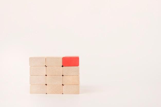 Czerwony drewniany klocek wyróżnia się z tłumu. przywództwo, myśl inaczej.