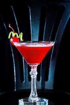 Czerwony drink koktajlowy z wiśnią w kieliszku do martini, skórka z wiśni i limonki.