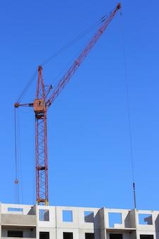Czerwony dźwig i błękitne niebo na placu budowy