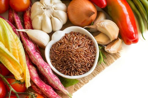 Czerwony ekologiczny ryż w misce i świeże warzywa z bliska