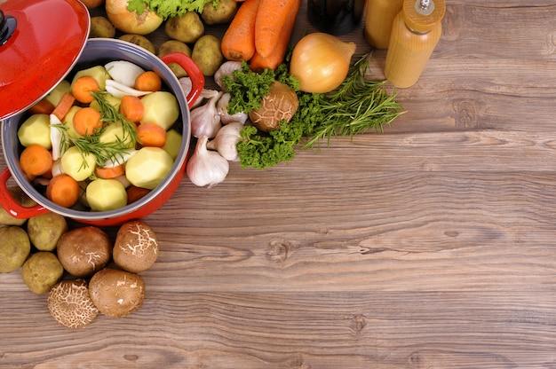 Czerwony garnek garnek z warzywami i ziołami