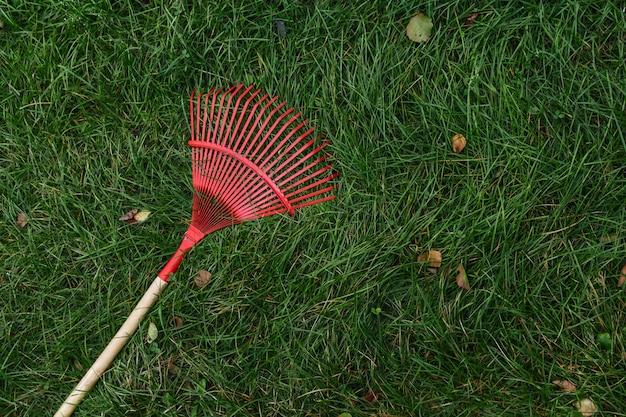Czerwony grabie do zbierania liści leżał na zielonej trawie. widok z góry. jesień, sprzątanie, letnia rezydencja. copyspace.