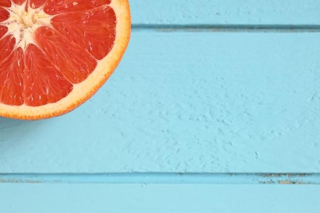 Czerwony grejpfrut pokroić na pół na niebieskim drewnianym tle rustykalnym.