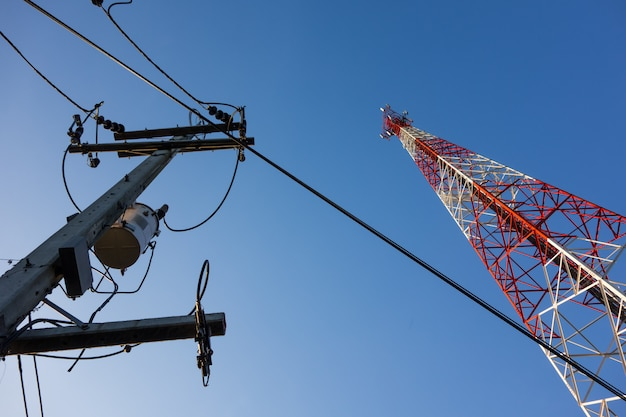 Czerwony i biały maszt z antenami komunikacyjnymi na niebieskim niebie