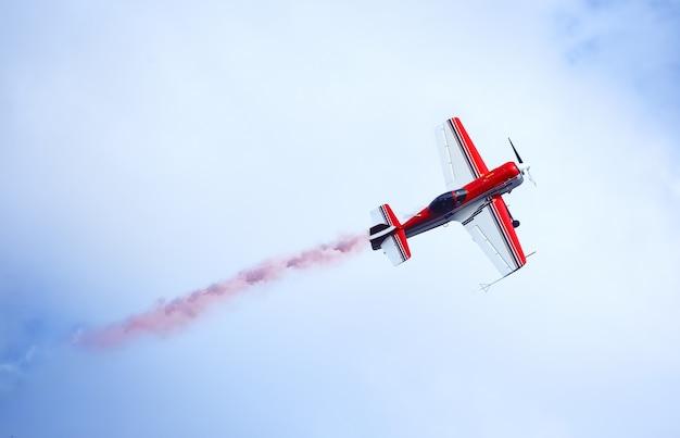 Czerwony i biały samolot emitujący kolorowy dym na niebie