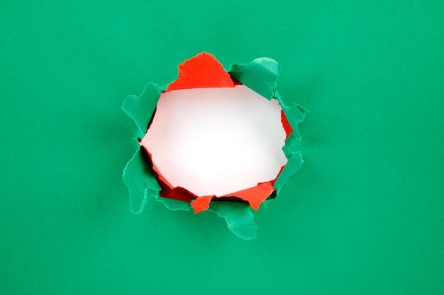 Czerwony i zielony dziura w papierze z podartymi bokami. boże narodzenie w tle