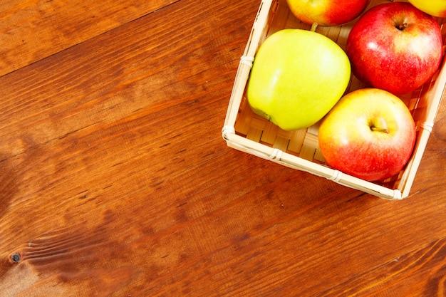 Czerwony jabłka zbliżenie w drewnianym koszu. widok z góry. wolne miejsce na tekst.