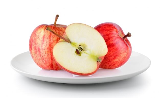 Czerwony jabłko w talerzu odizolowywającym na białym tle