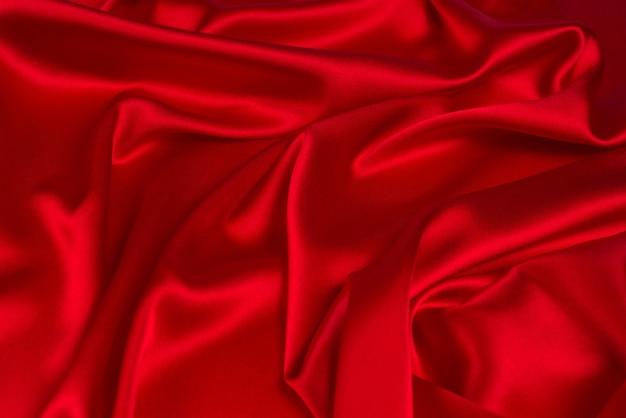 Czerwony jedwab lub satynowa luksusowa tekstura tkanina może służyć jako abstrakcyjne tło. widok z góry.