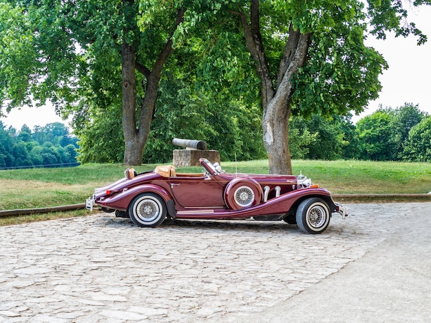 Czerwony kabriolet klasyczny zabytkowy samochód z akcentami w słoneczny dzień.
