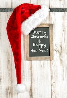 Czerwony kapelusz świętego mikołaja i rocznika tablica. dekorację świąteczną w stylu retro. przykładowy tekst wesołych świąt i szczęśliwego nowego roku!