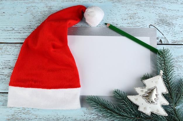 Czerwony kapelusz świętego mikołaja z gałązką jodły, kartą i ołówkiem na kolorowym drewnianym stole