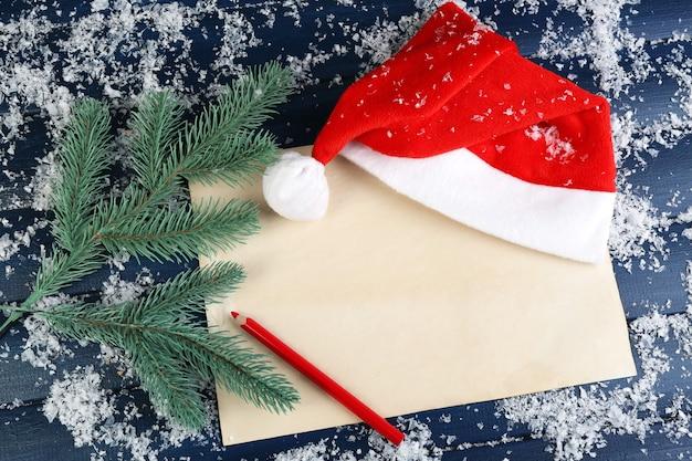 Czerwony kapelusz świętego mikołaja z gałązką jodły, kartką papieru, ołówkiem i płatkami śniegu na kolorowym drewnianym stole