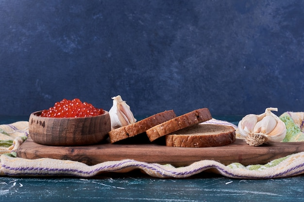 Czerwony kawior na drewnianej desce z kromkami chleba.
