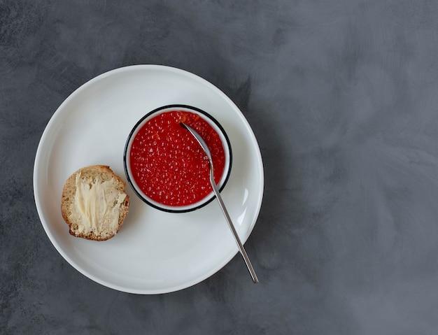 Czerwony kawior na talerzu, przysmaki z owoców morza. ciemne tło. widok z góry. kopia przestrzeń.