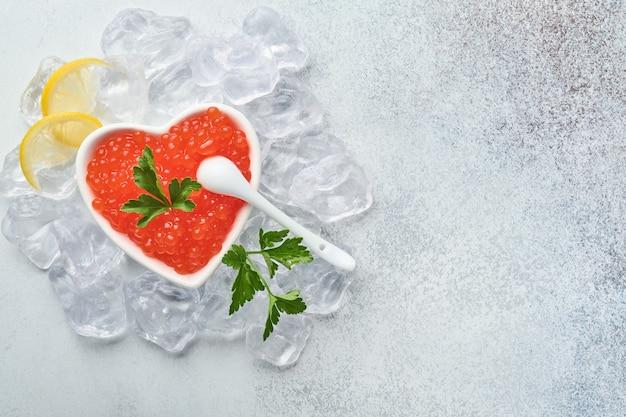 Czerwony kawior w misce w kształcie serca podawany z cytryną i kostkami lodu na szarym tle.