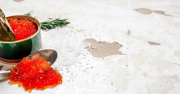 Czerwony kawior w słoiku z łyżką na rustykalnym tle