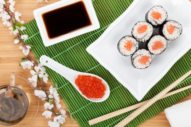 Czerwony kawior, zestaw do sushi, gałązka sakura i zielona herbata na bambusowym stole
