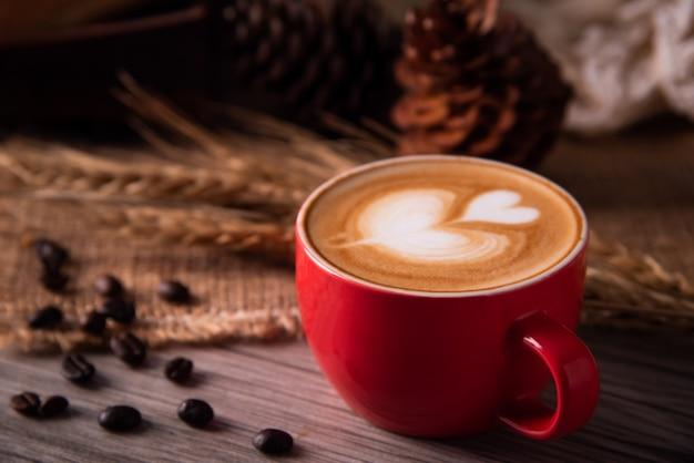 Czerwony kawowy szkło opiera się na drewnianej podłoga. koncepcja martwa natura