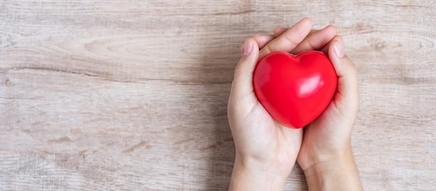 Czerwony kierowy kształt na drewnianym. opieka zdrowotna i koncepcja światowego dnia serca