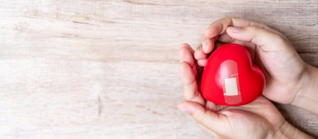 Czerwony kierowy kształt na drewnianym tle. koncepcja opieki zdrowotnej i światowy dzień serca